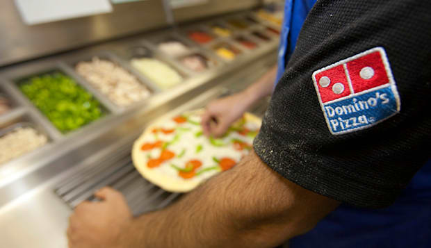 A Domino's Pizza employee preparing a fresh pizza ready for the cooking oven.