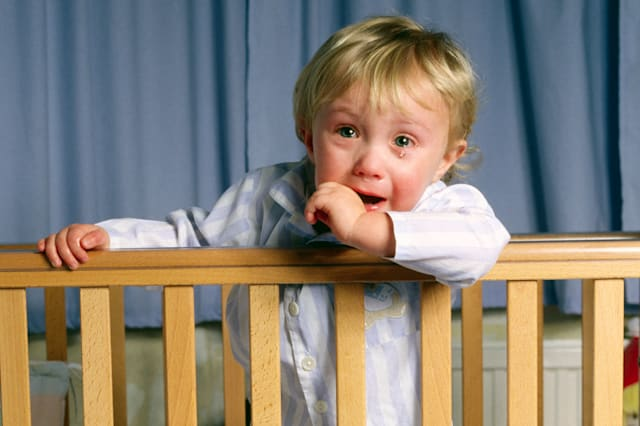 Toddler aged 2 years upset in cot