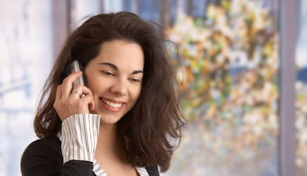 Happy young pregnant woman working in office, talking on mobile phone ...