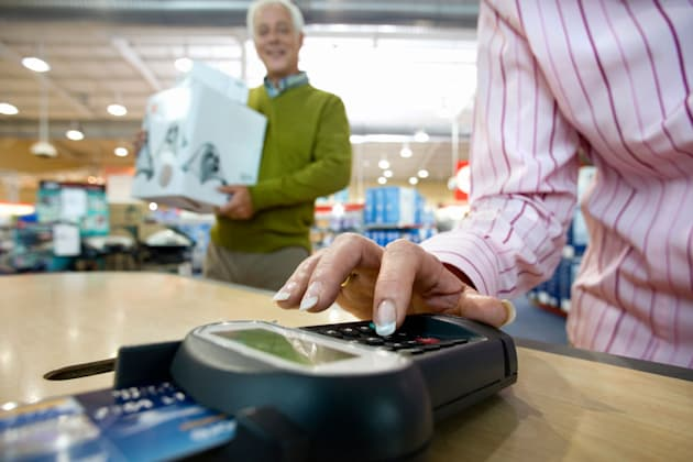 B0BKYT Woman paying with chip and pin by man with boxes, low angle view woman; paying; chip; pin; man; box; close; up; color; im