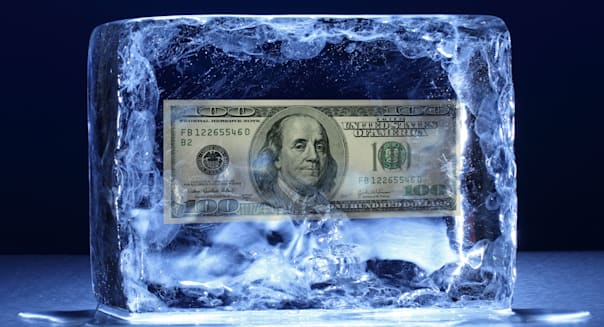 A frozen block of ice on a metal surface with 100 USD dollar banknote inside
