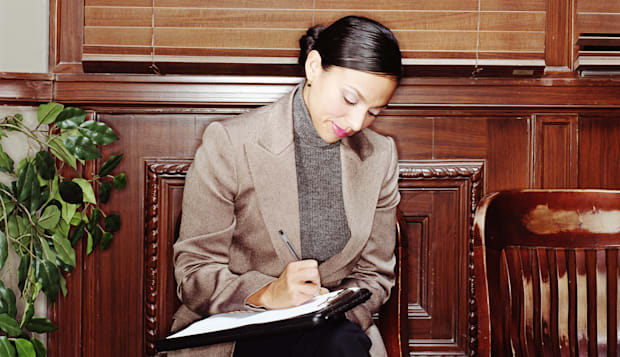 Woman sitting on chair, writing on clipboard