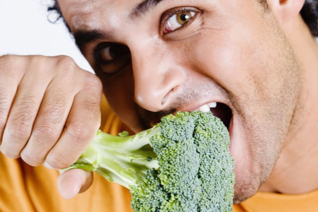 Portrait of a young man eating a broccoli