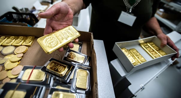 An employee returns a box of one kilogram gold bars to the safe from Swiss manufacturer Argor Hebaeus SA, in this arranged photograph at the Hungarian bullion dealers AranyPiac in Budapest, Hungary, on Monday, June 17, 2013. Hedge funds cut wagers on a gold rally for the first time in three weeks on mounting speculation central banks will curb record stimulus and as this year's slump in bullion spurred losses for billionaire John Paulson. Photographer: Akos Stiller/Bloomberg via Getty Images