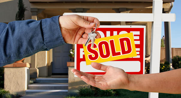Handing Over the Keys to A New Home with Sold Home For Sale Sign.