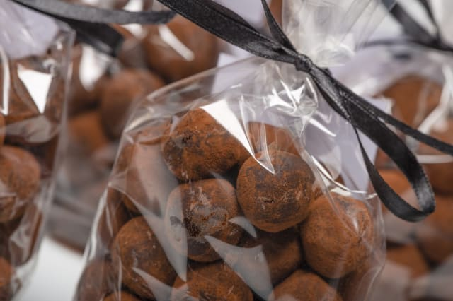 Closeup of chocolate truffles in luxury plastic bags with black ribbon. Christmas gifts. Shooting on white background in studio.