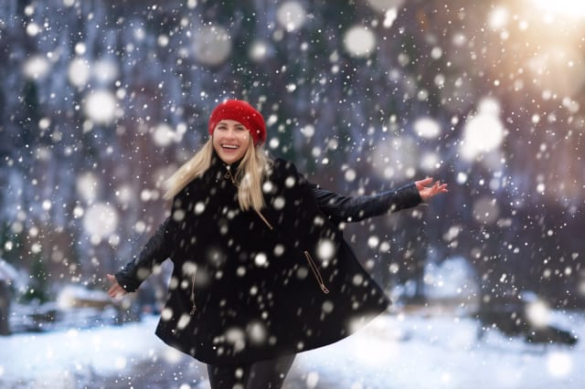 happy and energic woman in winter day enjoying the snowflakes and the december.wearing warm clothing, expressing positivity.phot