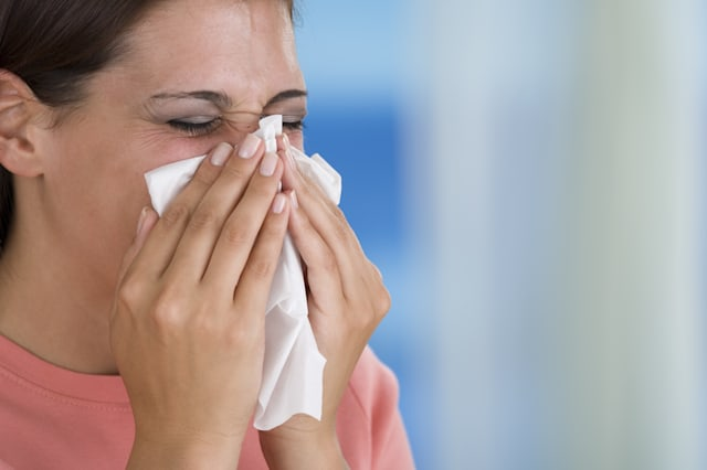 Woman blowing nose into tissue