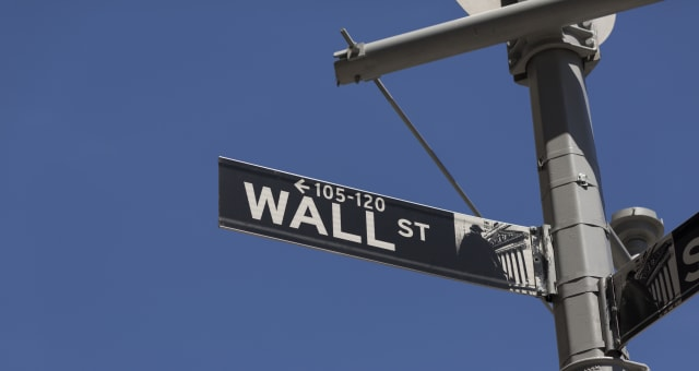 A daytime view of a Wall Street, street sign. The image has graphic composition.