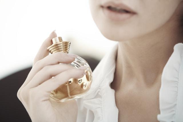 Woman applying and testing perfume