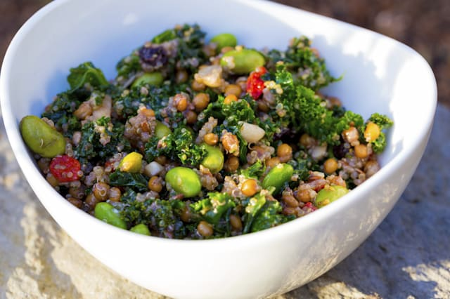 Raw paleo quinoa kale salad in a bowl. Healthy eating diet food.