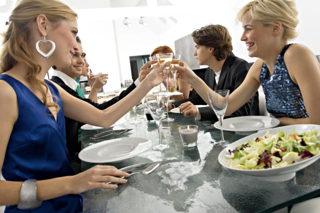 Group of people toasting with champagne at a dinner party
