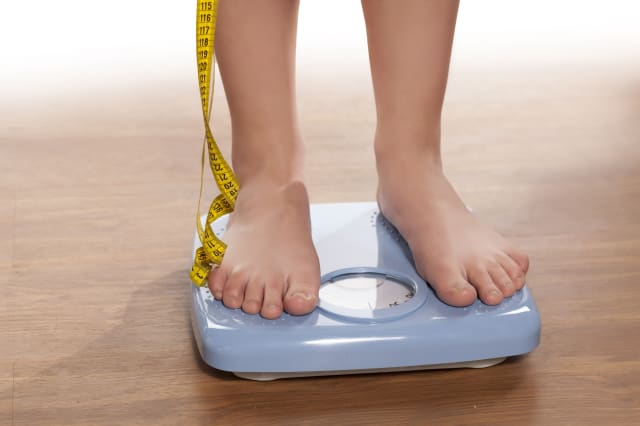 woman's legs on a domestic weight scale