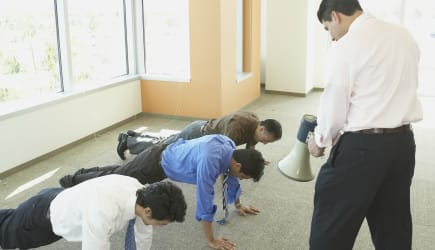 Businessman with megaphone making coworkers do pushups
