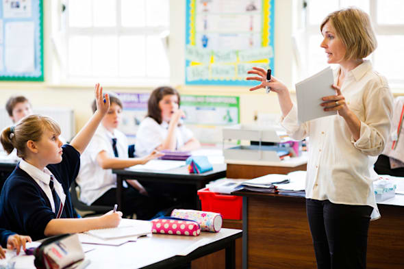 A woman teaching her pupils in a secondary comprehensive school , Wales UK