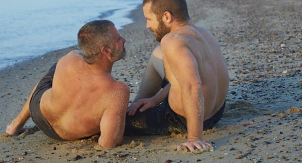 Gay Couple Sitting on Beach