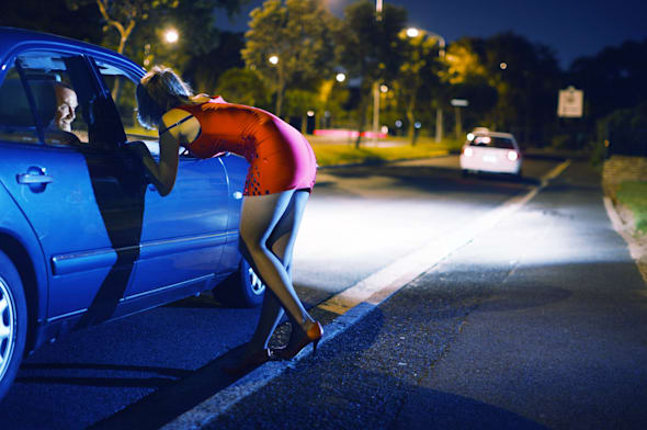 Young prostitute wearing red propositions man in car