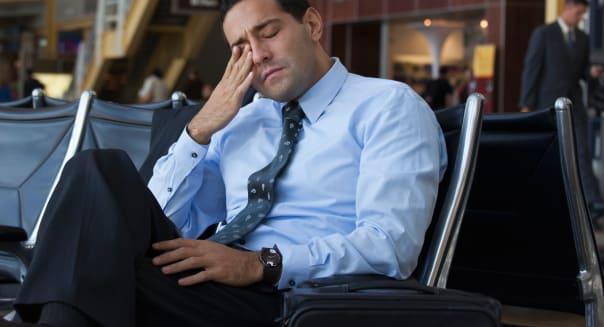 Tired Hispanic business traveler in airport