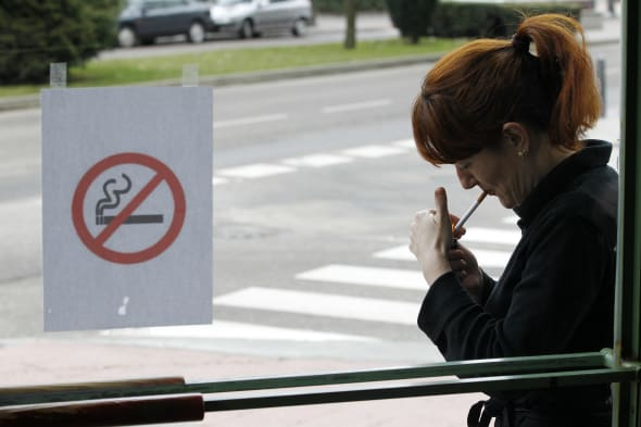 A woman lights a cigarette outside a caf