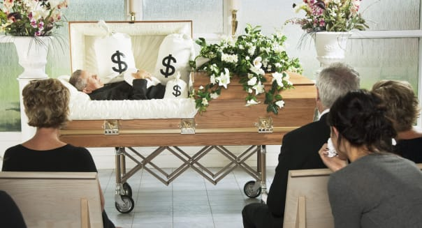 The Deceased Laying In A Coffin At His Funeral With Bags Of Money Surrounding Him