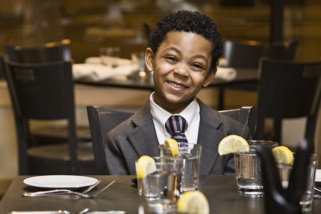 Boy (4-5) sitting at dining table, smiling, portrait