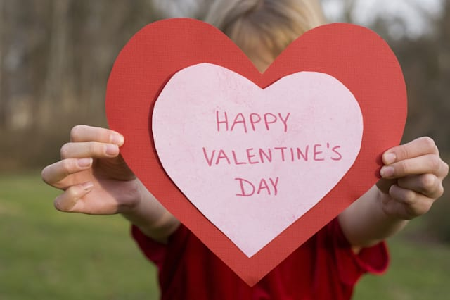 Girl with large handmade valentine heart card