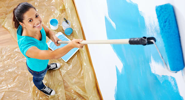 overhead view of woman painting new apartment standing on wooden floor