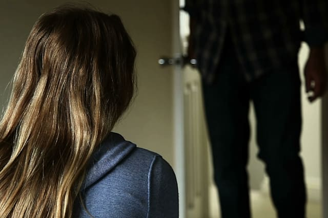 Anonymous man entering a dark room, a young girl sits in the foreground looking towards the door, back view.
