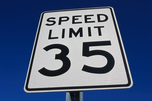 low angle view of a signboard with the speed limit on it
