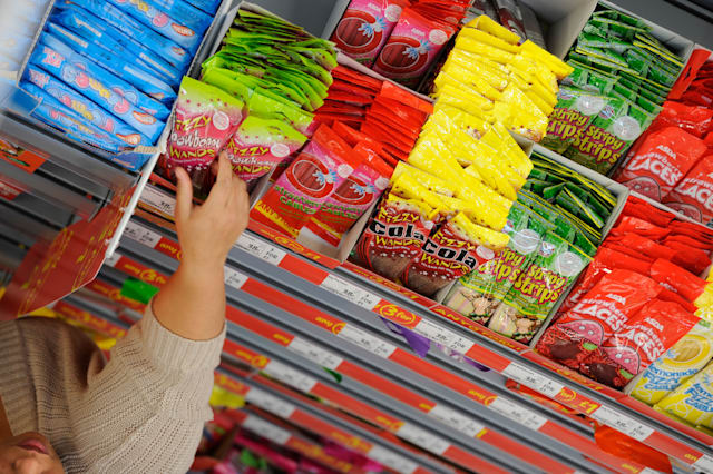 UK supermarket shelves stacked with sweets - a shopper reaches for a packet.