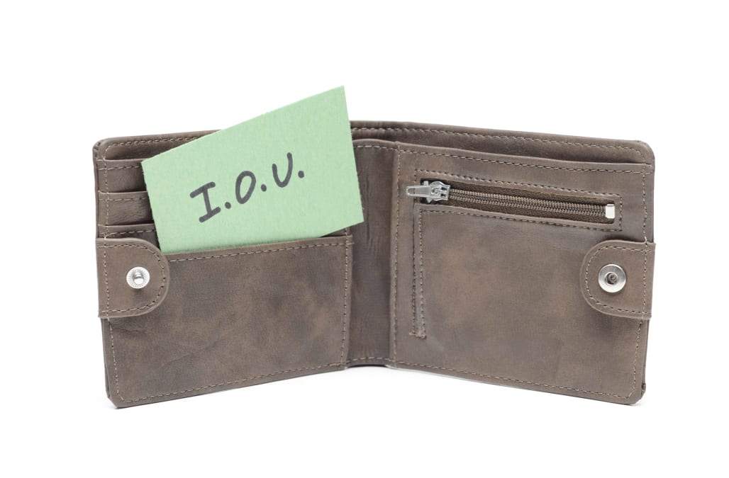 'Close up of an empty, open leather wallet with an I.O.U. message in it on a white background.'