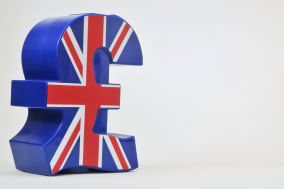 Blue plastic money box in the shape of the UK pound sterling symbol, with the Union Jack flag on the front. Studio shot against