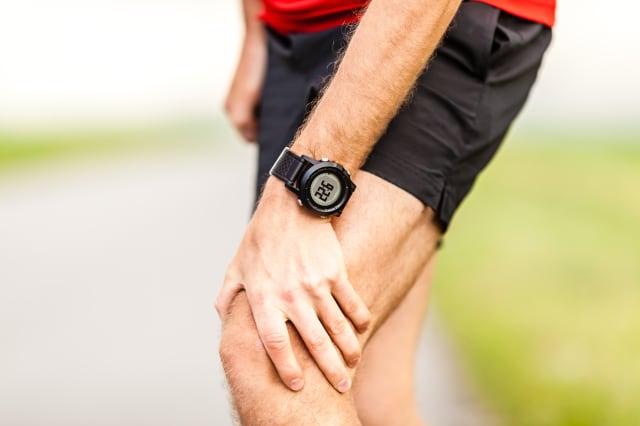 runner holding sore leg  knee...