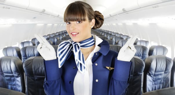 Young beautiful flight attendant smiling in the cabin