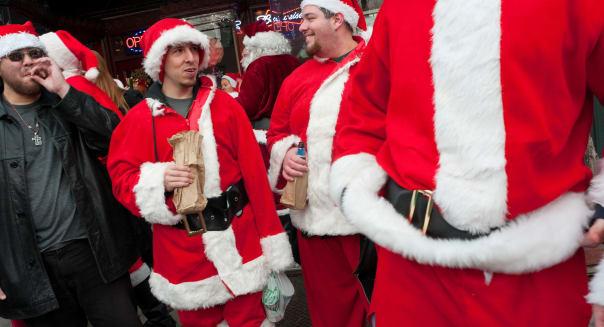 New York, NY - 11 December 2010 Naughty Santas drink beer and smoke cigarettes outside a Bleecker street bar during Santacon