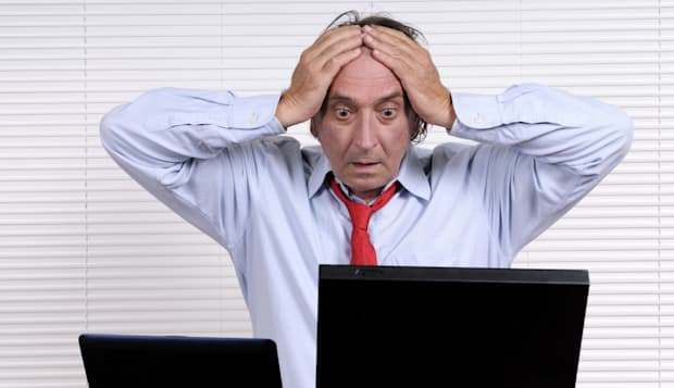 Stressed Businessman with Head in Hands Looking PC