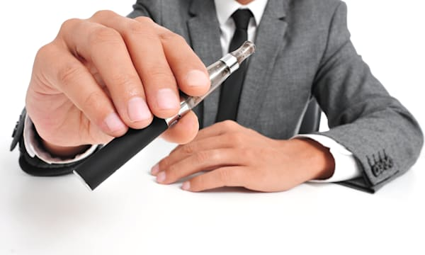 man wearing a suit vaping with...