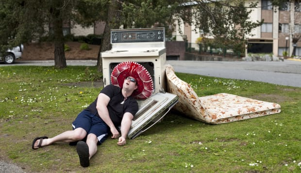 A young man who appears to be passed out amongst a pile of discarded junk, in a shady neighborhood.