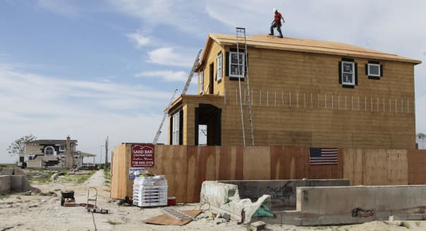 Superstorm Sandy Breezy Point (A worker walks the roof line of a house under construction in the Breezy Point community of New Y