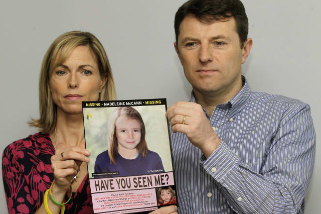 Kate and Gerry McCann pose for the media with a missing poster depicting an age progression computer generated image of their daughter Madeleine McCann