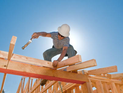 A carpenter installing roof trusses