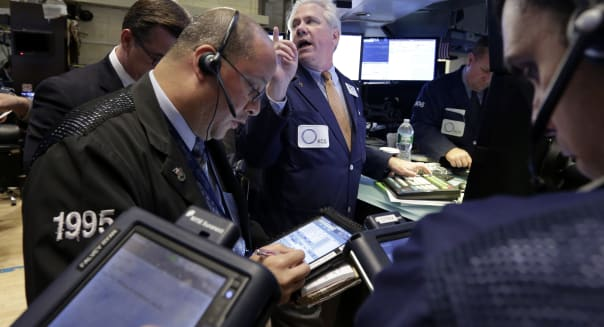 Wall Street (Specialist Brian Egan, background center, works with traders at his post on the floor of the New York Stock Exchang