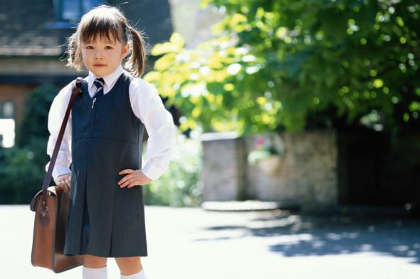 Girl (3-5) wearing school uniform, holding bag, outdoors, portrait