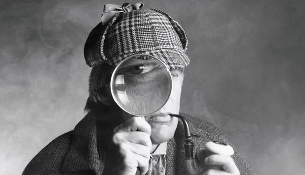Private investigator looking through magnifying glass