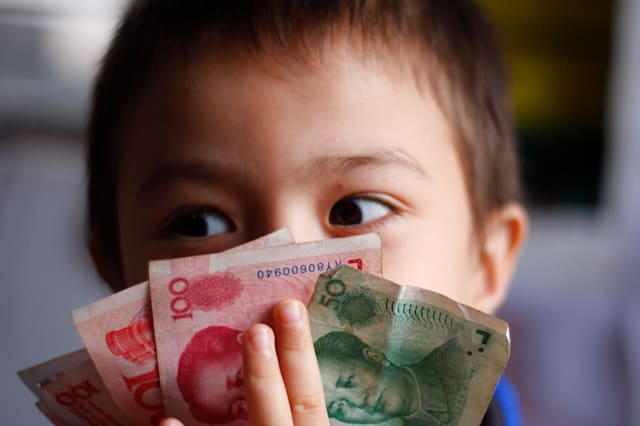 Boy playing with Chinese money