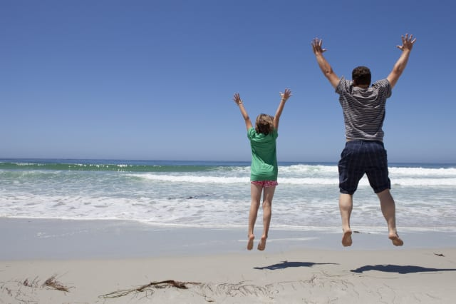 Father and daughter jumping at the beach