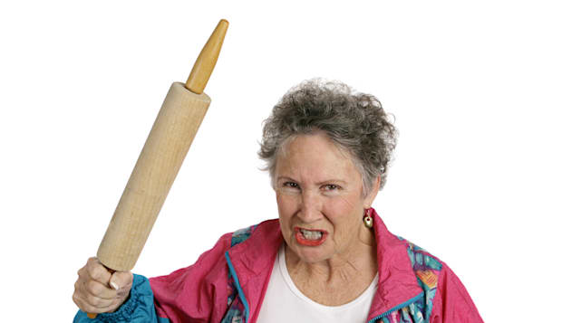 A very angry senior lady holding a rolling pin and threatening to whack someone with it her husband Isolated on white