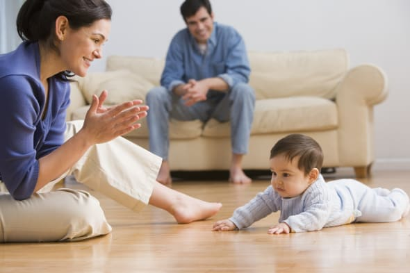 Mother clapping with baby on floor