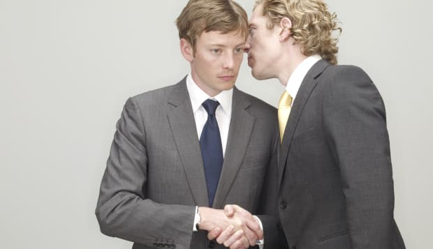 businessmen whispering and shaking hands