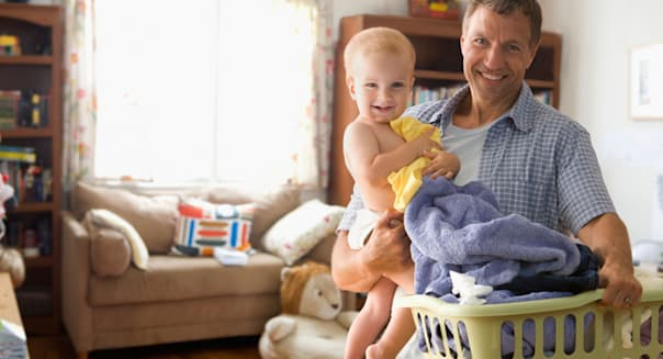 Caucasian father carrying son and laundry